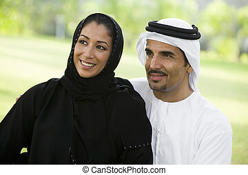 A Middle Eastern couple sitting in a park