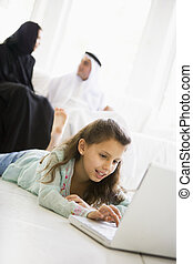 A Middle Eastern girl lying on the floor using a laptop