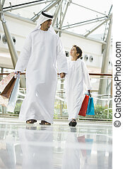 A Middle Eastern man and his son in a shopping mall