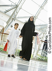 A Middle Eastern woman and her son in a shopping mall