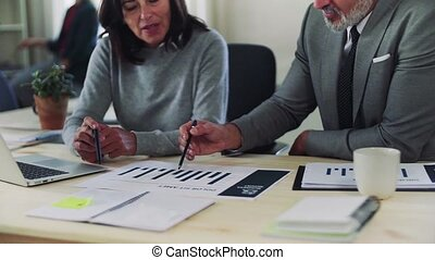 A midsection of businessman and businesswoman working together in office, talking.