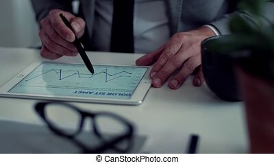 A midsection of businessman with tablet sitting at the table, working.
