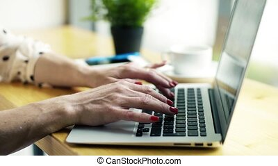 A midsection of woman with laptop sitting at the table in a...