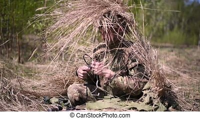A military man is camouflaged outside by putting on a...