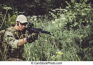 A military man or airsoft player in a camouflage suit sits in the grass and aims from an automatic rifle to the side