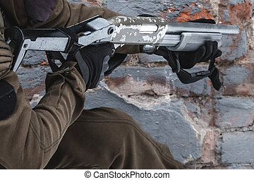 A military man with a shotgun aims at the target.
