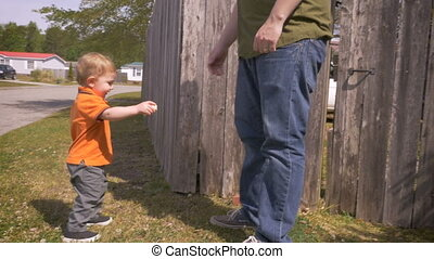 A millennial father reaches for his son's hand in suburban neighborhood