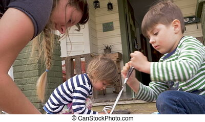 A millennial mother and her two young kids dyeing easter...