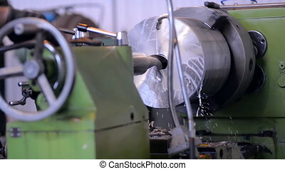 A milling machine operator working factory workshop makes some particular on steel