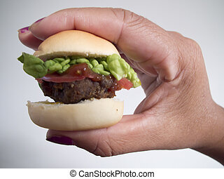 mini deluxe burger - A mini deluxe burger held in my wifes ...