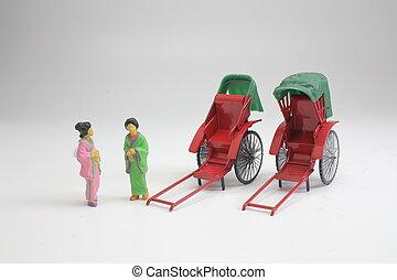 a Mini statue and red vintage oriental rickshaw cab