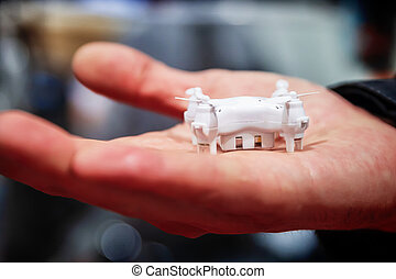 a miniature drone in hand
