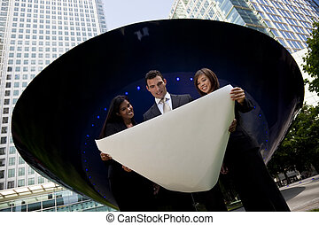 A mixed race team of one man, an Indian and Chinese Asian woman looking at an architectural plan outside in a modern city environment