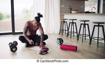 A mixed race young man doing exercise indoors at home, ...