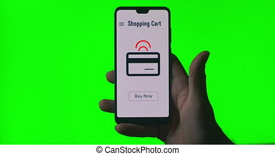 A mobile phone in the hands of a person with an animation on the screen about online purchase and payment. click the buy now button. Sending money via Internet banking. Green background for chromakey.