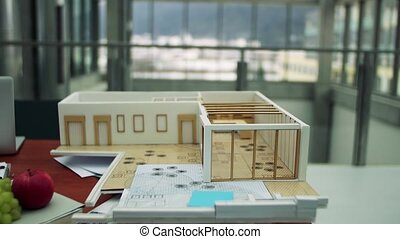A model of a house on the desk in an office. - A model of a...