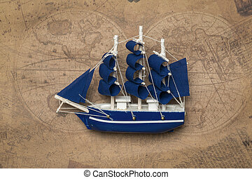 A model of a sailboat with blue sails on the background of an old map.