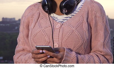 A modern girl types something on her smartphone