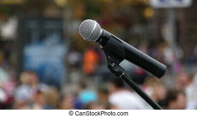 A modern microphone installed on a square full of people