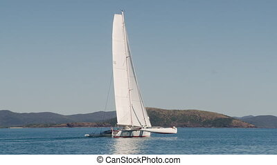 A modern sailboat sailing - A long shot of a white modern...
