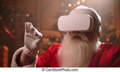 A modern Santa Claus sits in a chair and uses virtual reality technology to buy and send gifts to children.