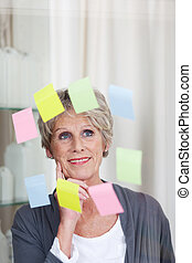A modern senior woman looking at sticky notes