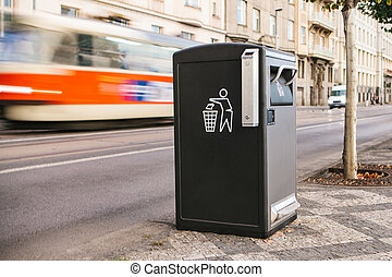 A modern smart trash can on the street in Prague in the Czech Republic. Collection of waste in Europe for subsequent disposal. Eco-friendly waste collection. In the background a tram is in motion.
