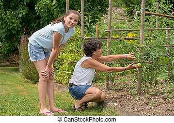 mom and her teen daughter in the vegetable garden