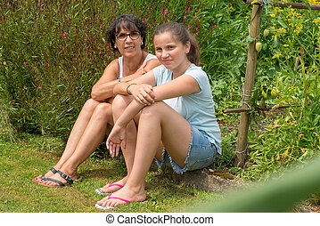 mom and her teen daughter sit in the grass