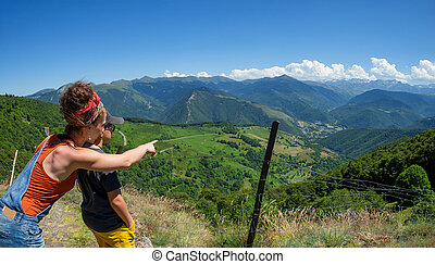mom and son looking view of valley Aure in the french pyrenees mountains
