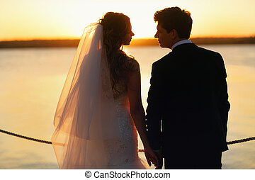 A moment before a kiss between newlyweds standing on the sea shore