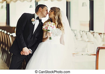 A moment before a kiss between pretty newlyweds