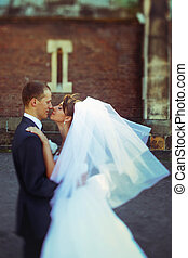 A moment before a kiss of newlyweds posing on the street