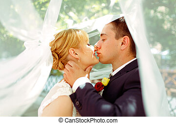 A moment before a kiss of newlyweds standing under a veil