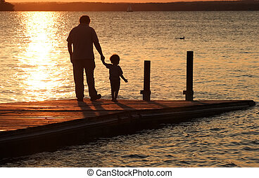 A father holds his son's hand as they walk out onto a dock at sunset.