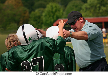 The football coach is talking to his players on the sidelines