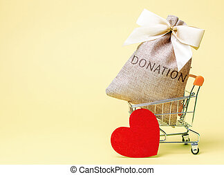 A money bag with the word Donation and a red heart. Accumulation of money for a medical donation. Health care. Saving. Social medical help from volunteers. Charitable foundation. Supermarket trolley.