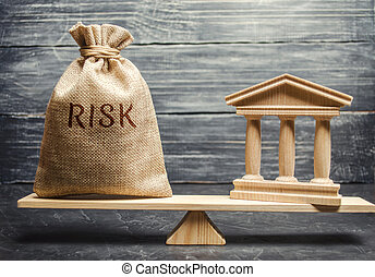 A money bag with the word Risk and a bank building on the scales. The concept of financial and economic risk. Unreliable investment. Unpaid loan. Financial risk management. Commercial loan