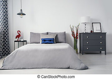 A monochromatic gray designer bedroom interior with a big bed and drawer cabinet and with contrasting accents of red gladiolas and blue quilted pillow. Real photo.