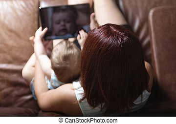 mother and baby are looking to play and read tablet computer on the couch at home