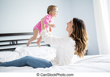 Mother and baby child on a white bed.