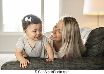Mother and baby daughter plays at home on the sofa