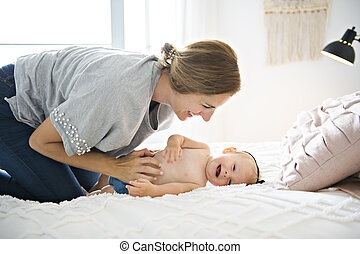 Mother and baby girl on a white bed