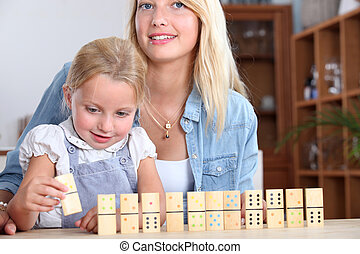 A mother and daughter playing with dominos.