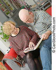 a mother and her adult son looking at a photo album on a sofa