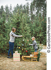 A mother and her child son decorate the Christmas tree outdoors, in winter forest. New Year decorations, wooden sledge with Christmas wreath, gifts under the tree