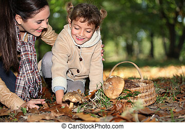 a mother and her little girl picking mushrooms in the forest