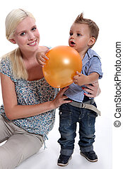 a mother and her little son playing with a balloon