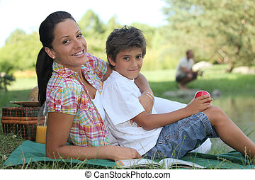a mother and her son at picnic, the father is fishing