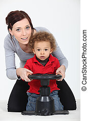 a mother and her son playing with a steering wheel
